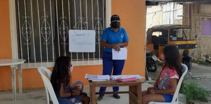 Carolina ESpinoza va en bicicleta a casa de sus alumnos que no tienen acceso a internet.