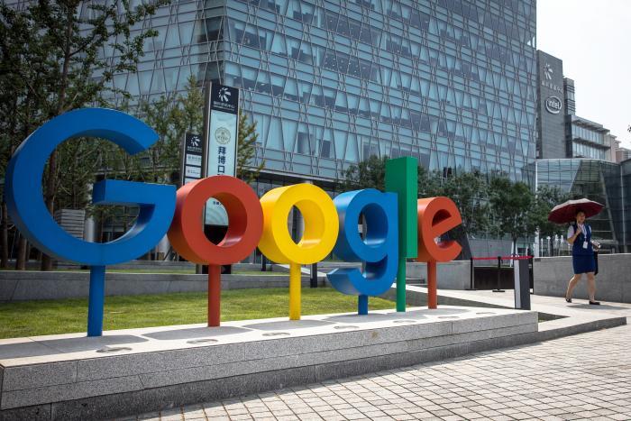 Fotografía de archivo fechada el 3 de agosto de 2018 que muestra a una mujer que camina junto al logo de Google, en las oficinas de dicha firma en Pekín (China).