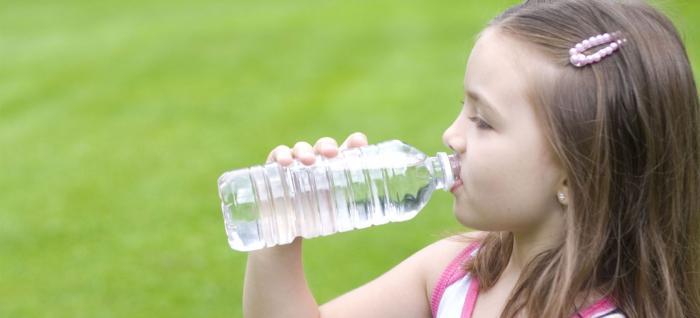 Niña se hidrata bebiendo agua