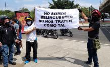 Dos motociclistas sostienen un cartel en el que piden no ser tratados como delincuentes.