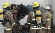 Bomberos ingresan al edificio para calmar las llamas.