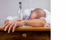 Hombre junto a botella de alcohol