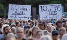 """Manifestantes sostuvieron carteles en los que se leen """"6 niños muertos y contando"""" (i) y """"10.796 mentiras y contando"""" (d) durante una manifestación en los exteriores de la Casa Blanca. La protesta del pasado viernes exigió el cierre de los centros de dete"""