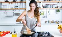 Mujer cocinando con alegría.