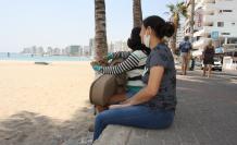 Dos jóvenes turistas contemplaban el mar este fin de semana, sin poder ingresar, por las restricciones de los COE cantonales.