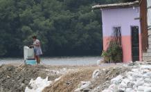 Una lavadora de ropa, junto al brazo de mar y frente al manglar que cubre la zona.