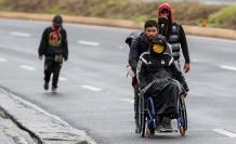 Ciudadanos venezolanos, uno de ellos con discapacidad, transitan por una carretera cercana a Quito (Ecuador).