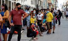 Grupos de personas con tapabocas hacen fila para comprar en un mercado, el 11 de marzo de 2021, en La Habana (Cuba).