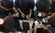 """Estudiantes tailandeses juegan al videojuego """"""""Pokemon Go"""""""" desde su teléfono móvil en un centro comercial en Bangkok, Tailandia."""