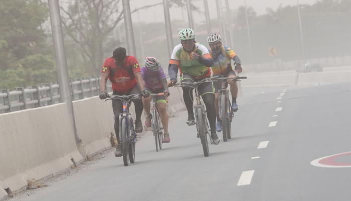 Ciclistas conducen en medio de las partículas del Sangay, en Guayaquil.
