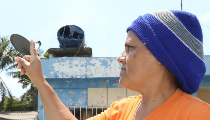 Janeth Maenza muestra su tanque de agua derretido por el calor. Su casa está a seis metros del incendio.
