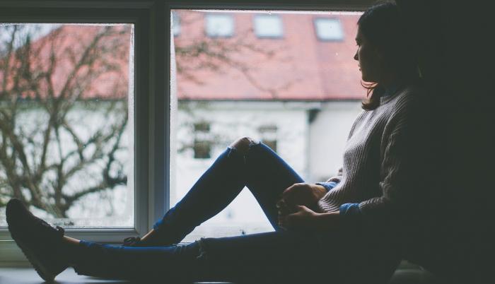 Mujer sentada frente a una ventana