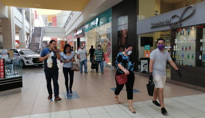 Dos personas sin mascarillas en un mall