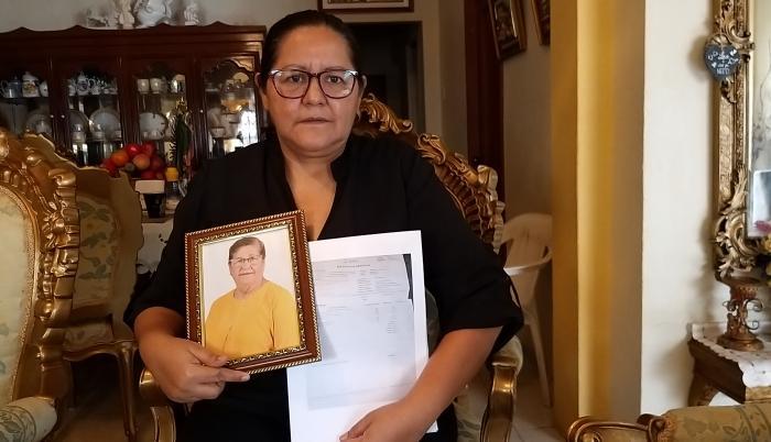 Elsa Maldonado sostiene un retrato de su madre y los papeles de defunción.
