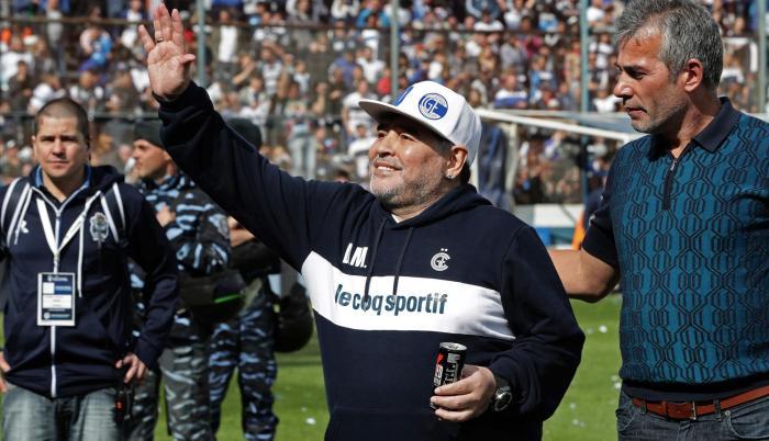 La estrella del fútbol argentino Diego Maradona saluda al público junto al presidente Gabriel Pellegrino.
