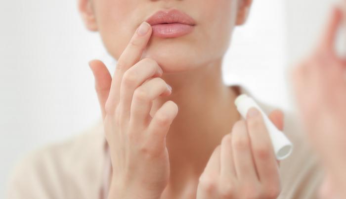 Mujer aplica bálsamo a sus labios