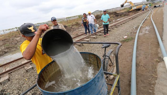 Algunos moradores aprovecharon la rotura de una tubería, a la altura de la cooperativa 28 de Agosto en Durán, para recolectar agua que, aunque sucia, dijeron les servía para trabajar, sobre todo, en el área de construcción.