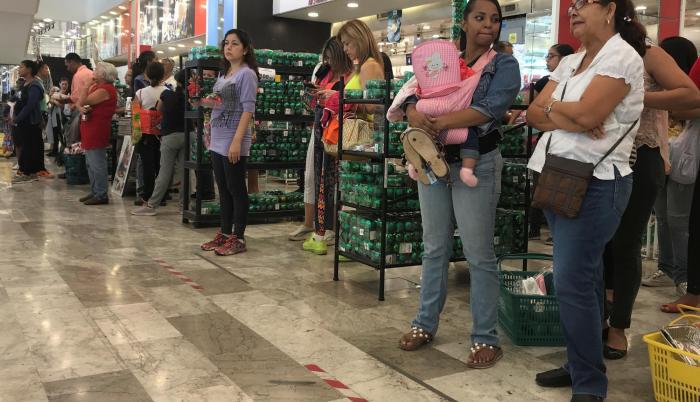 Un grupo de personas espera para pagar sus compras en un local de Caracas.
