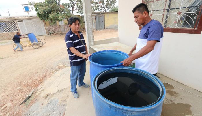Alternativa. El usuario Nelson Quimí (derecha) recurre a los tanqueros para abastecerse de agua.