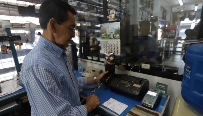 Negocios. Orlando Almeida muestra el teléfono fijo de su negocio y se lamenta de que no funcione la línea.