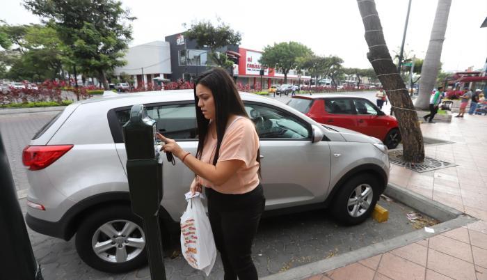 Gestión. Emily Avilés coloca unas monedas al parquímetro antes de comprar en un local de Plaza Triángulo.