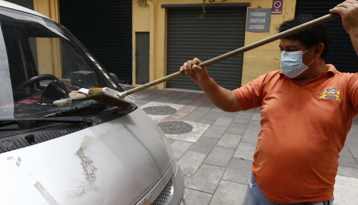 Un ciudadano de Guayaquil retira las cenizas del volcán en un barrio de Guayaquil.