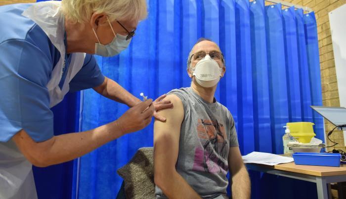 David Farrell, paciente de 51 años, recibe una de las dos vacunas de Pfizer y BioNtech en un centro de vacunación en Cardiff (Reino Unido).