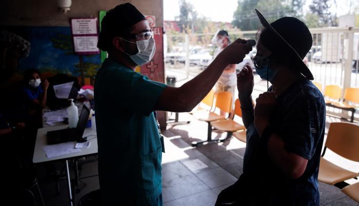 Un enfermero toma la temperatura a una mujer antes de su ingreso a un centro de salud en Santiago (Chile)