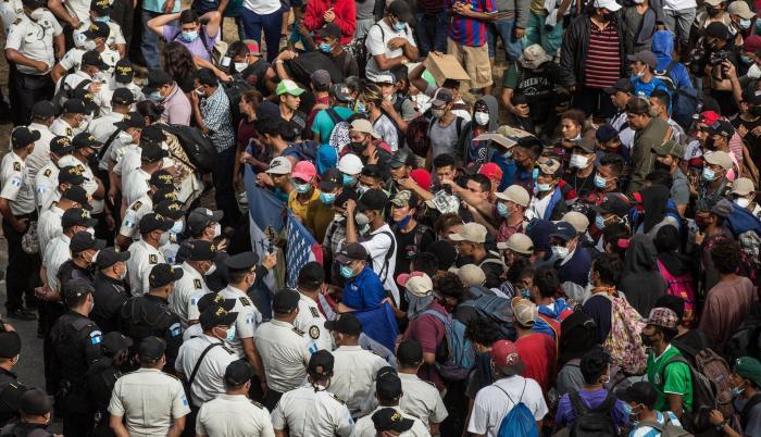 Migrantes hondureños se arrodillan para orar frente a los policías guatemaltecos, el 17 de enero de 2021 desde la aldea Vado Hondo, Chiquimula (Guatemala).