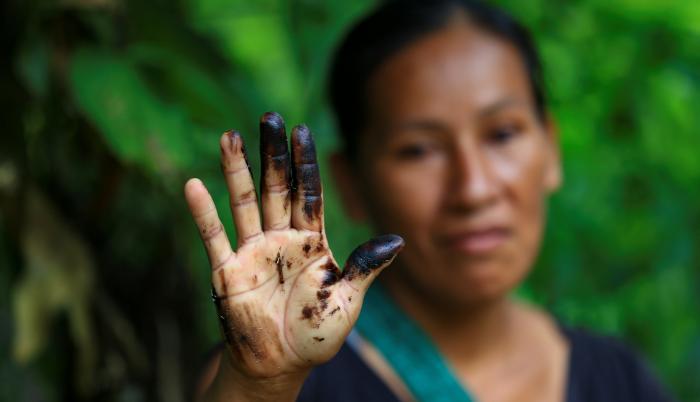 Una indígena de la comunidad de Amarumesa muestra en su mano residuos de petróleo en la Amazonía ecuatoriana.