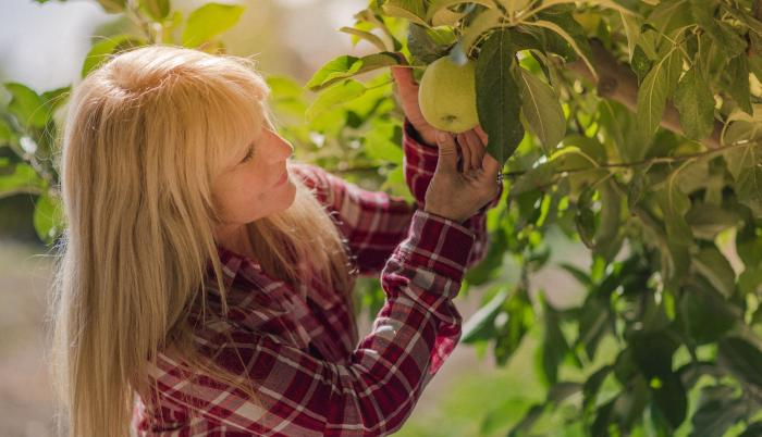 Mujer cogiendo una fruta