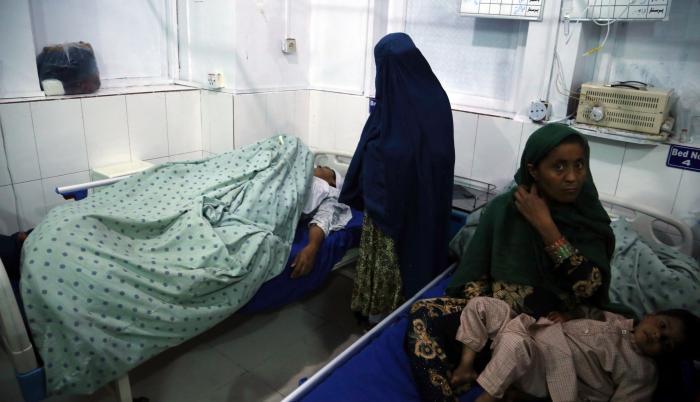 Una mujer recibe atención médica tras resultar herida en uno de los dos asesinatos selectivos perpetrados contra tres presentadoras de televisión afganas que murieron tiroteadas, en Jalalabad.