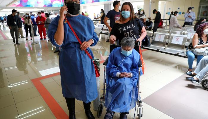 Una adulta mayor espera el 25 de marzo de 2021 para ser vacunada contra la covid-19, acompañada por una familiar en el Hospital Luz Elena Arismendi de Quito (Ecuador).