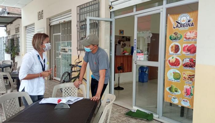 Visita. Funcionaria municipal habla con el administrador de un local.