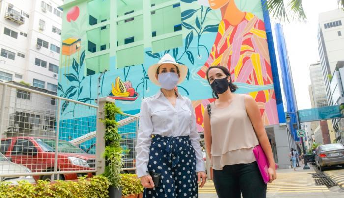 La gerente de la Empresa Pública de Turismo, Gloria Gallardo (i), frente a un mural de la calle Panamá.