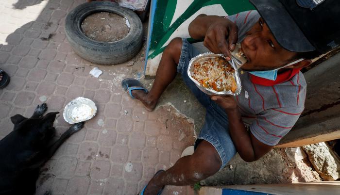 Henrique Silva, de 22 años, almuerza tras recibir una donación de comida en la calle da Paz, el 2 de abril de 2021 en la favela de Paraisópolis, en Sao Paulo (Brasil).