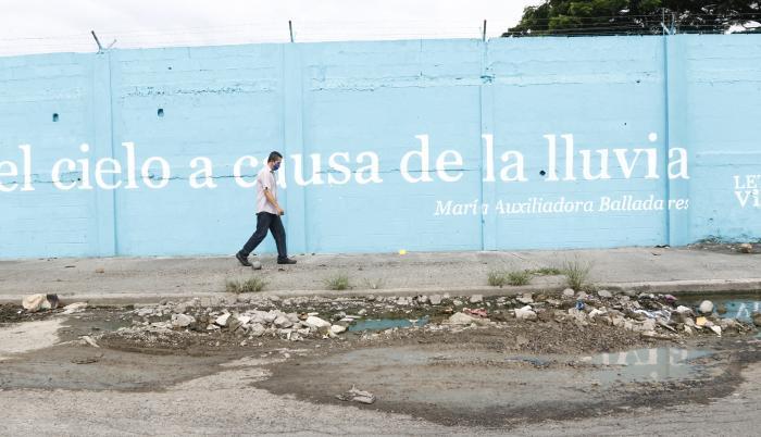 Un aspecto del suburbio muestra el costoso proyecto Letras Vivas junto a un bache.