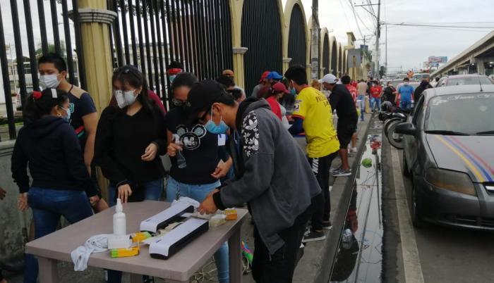 En la medida que llegan más ciudadanos a votar se forman los grupos que buscan plastificar la cédula de votación.